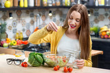 Young smiling woman making healthy fresh salad in the modern kitchen interior full of fruits and vegetables