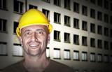 Freundlich lächelnder Arbeiter vor Baustelle - 129235717