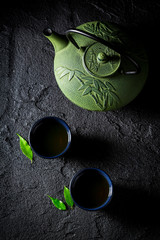Aromatic green tea in Asian restaurant on black rock