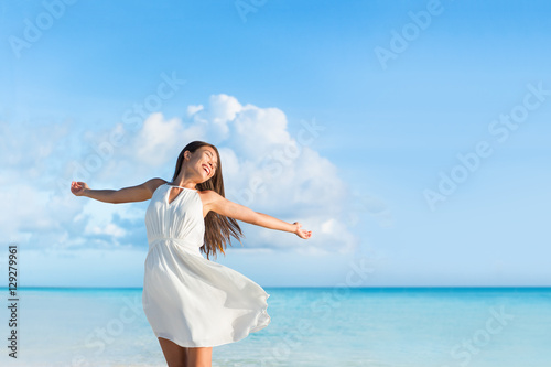 Leinwanddruck Bild Freedom young woman with arms up outstretched to the sky with blue ocean landscape beach background copy space. Asian girl in white dress dancing carefree in sunset.