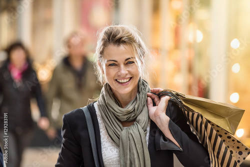 Poster Middle age woman holding shopping bags and walking in the street