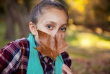 Portrait of girl hiding mouth with autumn leaf