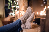 Fototapety Feet of unrecognizable woman in socks by the Christmas fireplace