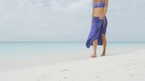 Beach asian woman in fashion beachwear white cover-up skirt clothing. Asian girl tourist wearing blue pareo for and white sun hat for sun protection relaxing walking in ocean water on vacation travel.
