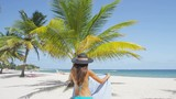 Woman on beach walking with floppy sun hat and towel for sunbathing. Girl wearing bikini relaxing on beach on Barbados, Caribbean. RED EPIC SLOW MOTION.