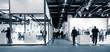 Leinwanddruck Bild - Blurred business people trade fair stands