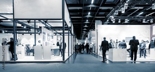 Leinwanddruck Bild Blurred business people trade fair stands