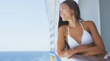 Young woman in swimsuit standing on cruise ship at sunny day looking at sea. Beautiful mixed race Asian Chinese / Caucasian girl enjoying vacation travel on ocean liner. RED EPIC SLOW MOTION.
