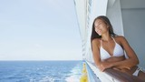 Cruise woman enjoying luxury travel lifestyle from cruise ship balcony. Beautiful lady in bikini smiling happy looking at view of ocean enjoying her holidays at sea. RED EPIC SLOW MOTION.