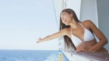 Cruise ship travel woman in bikini cheering joyful enjoying cruise ship holidays. Mixed race Asian Chinese / Caucasian woman traveling on cruise liner excited cheerful on balcony. RED EPIC SLOW MOTION