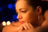 Beautiful woman getting spa massage by candle light