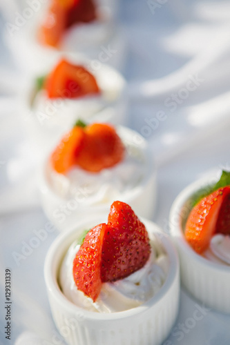 Poster Cupcakes with whipped cream decorated with strawberry