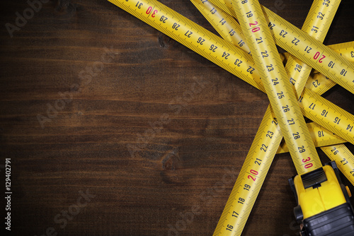 Poster Tape Measures on Brown Wooden Background