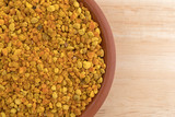 Bowl of bee pollen granules on a wood table top close view.