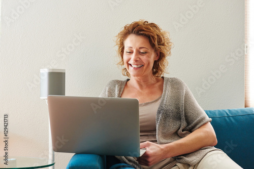 Woman sitting on couch with laptop at home © mimagephotos