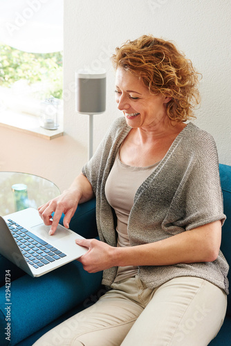 Smiling woman using laptop sitting on couch © mimagephotos