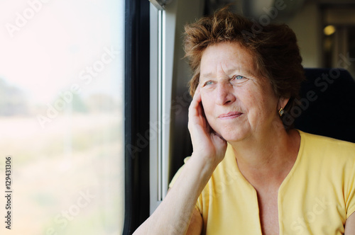 Portrait of beautiful 70 years old woman sitting in the train Poster