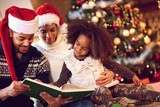 mother, father and daughter read a book at fireplace on Christma