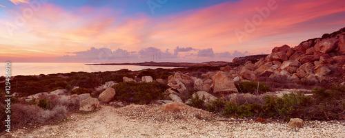 Poster Oranje eclat Cyprus beautiful sunrise with rocks and cloudy colorful sky, natural sea panoramic background
