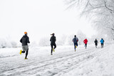 group young people running together snowy trail in winter Park. rear view