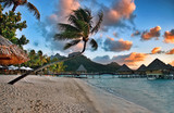 Beautiful sunset sunrise tropical beach scene with palm trees, bungalows - 129486181