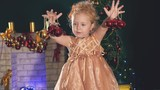 Cute little girl dancing, background decorated Christmas tree