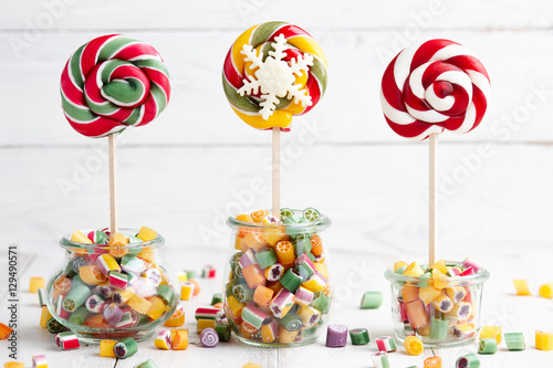 Colorful lollipops and candy canes in glass jars on white wooden background Poster