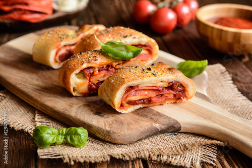 Poster Traditional Italian Stromboli stuffed with cheese, salami, green onion and tomat
