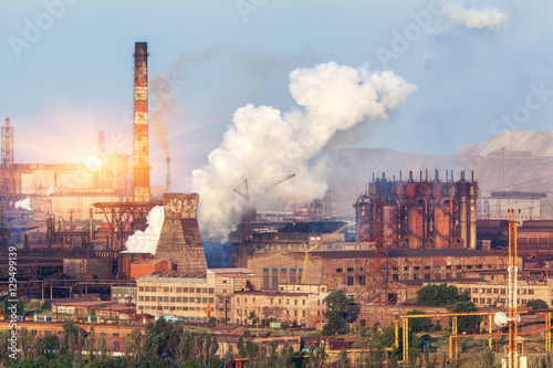 Tuinposter Canyon Metallurgy plant in Ukraine at sunset. Steel factory with smog. Pipes with smoke. Steel mill. Heavy industry factory. Metallurgical plant in city. Steel works. Ecology problems, atmospheric pollutants