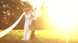 Bride and groom walking outdoors at sunset