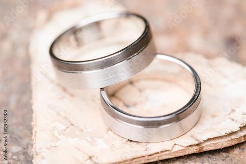 silberne Eheringe auf Herz aus Holz © Kusel