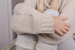 Closeup of girl's hands in casual wool sweater hugging her knees to her chest, feeling lonely