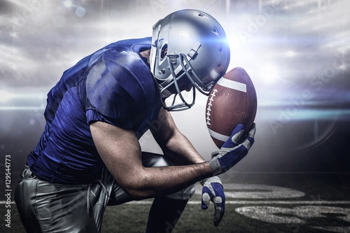 Fototapeta Composite image of upset american football player with ball