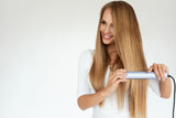 Beautiful Woman Ironing Long Straight Hair With Straightener