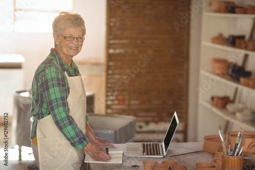 Poster Portrait of female potter making note from laptop