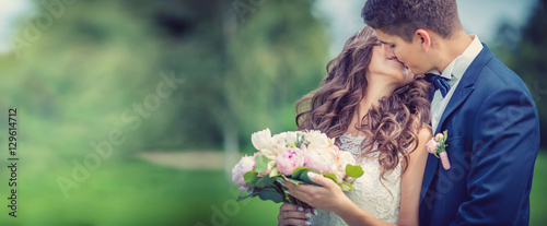 Beautiful young bride and groom kissing in park