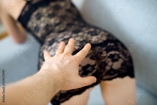Man's hand trying to touch sexy woman butt.