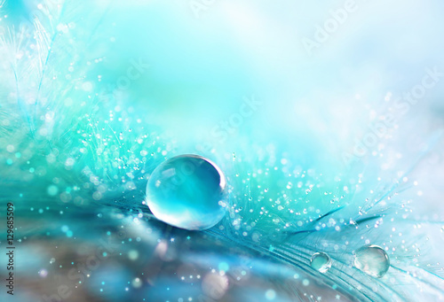 A drop of water dew on a fluffy feather close-up macro with sparkling bokeh on blue blurred background. Abstract romantic delicate magical artistic image for the holiday, cards, christmas, new year.
