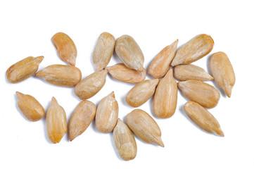 peeled sunflower seeds on white surface.