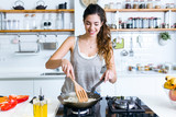 Young woman frying onion into the pan in the kitchen. - 129787725
