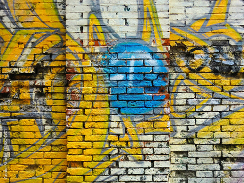Brick building exterior wall texture with spray paint graffiti