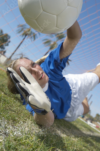 Young female soccer goalkeeper diving to block a goal attempt Poster
