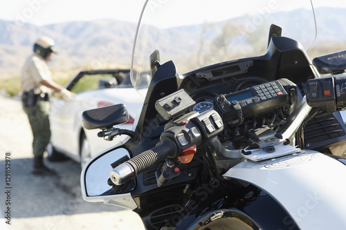 Blurred police officer talking to driver of stopped car on desert highway with f Poster
