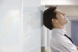 Unhappy businessman leaning back against office wall and looking at ceiling - 129864942