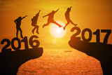Silhouette group of young mans jumping between 2016 and 2017 years with beautiful sunset at the sea.