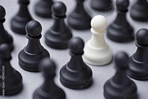 Poster Single white chess pawn amongst black ones
