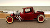 Classic Hot Rod  pickup truck on seafront promenade with sea in background - 129939988