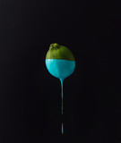 Fototapety Lime with dripping blue paint on dark background. Minimal food c