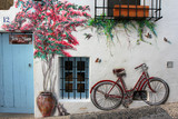 Cute background with street art on the white wall: bicycle, kitten and flowers.  - 129954364