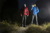 Fototapety Full length portrait of male hikers with flashlights in field at night